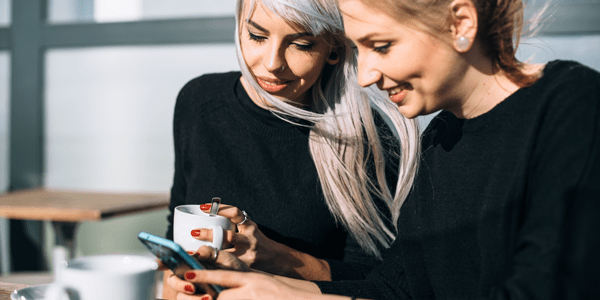 Two women looking at a cell phone over coffee