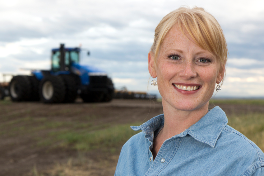 Smiling young female farmer with a tractor