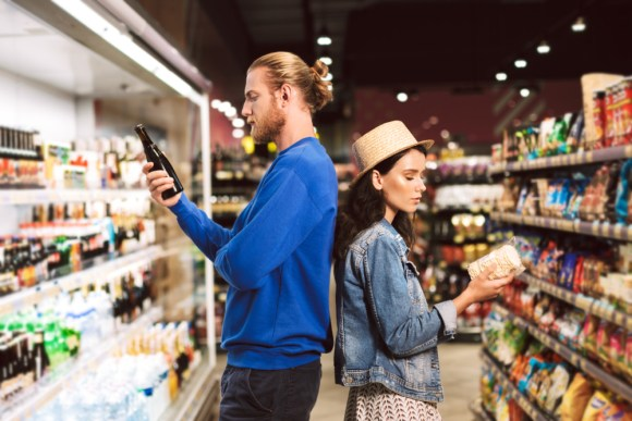 A young couple carefully reading food labels in a grocery store