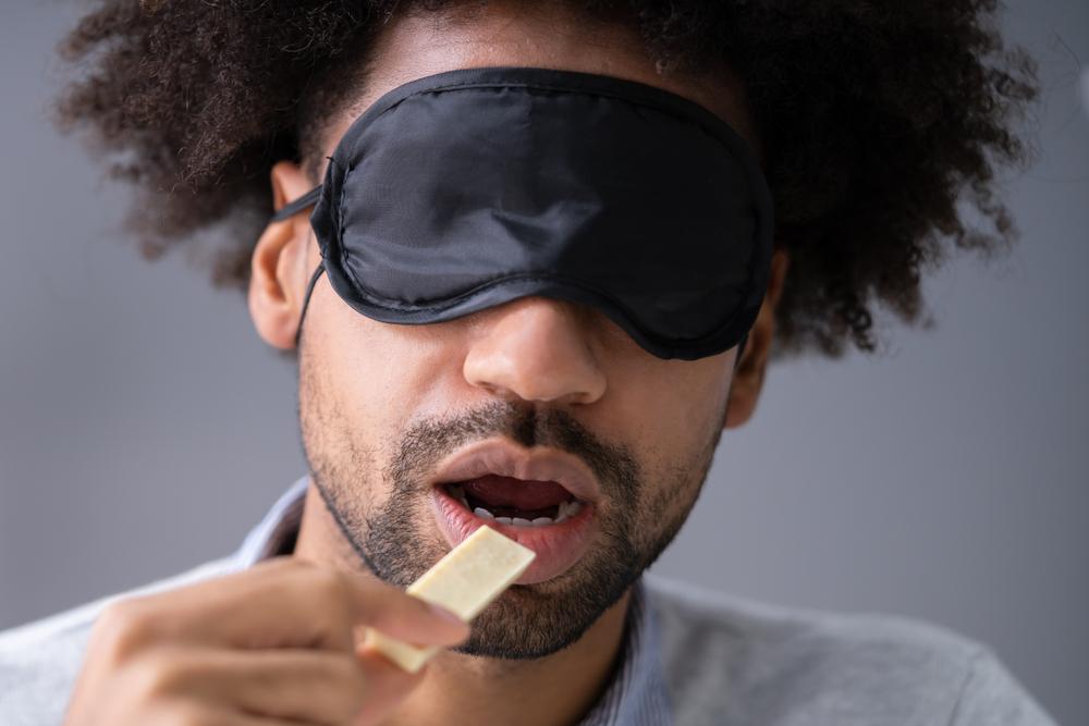Blindfolded man tastes food sample