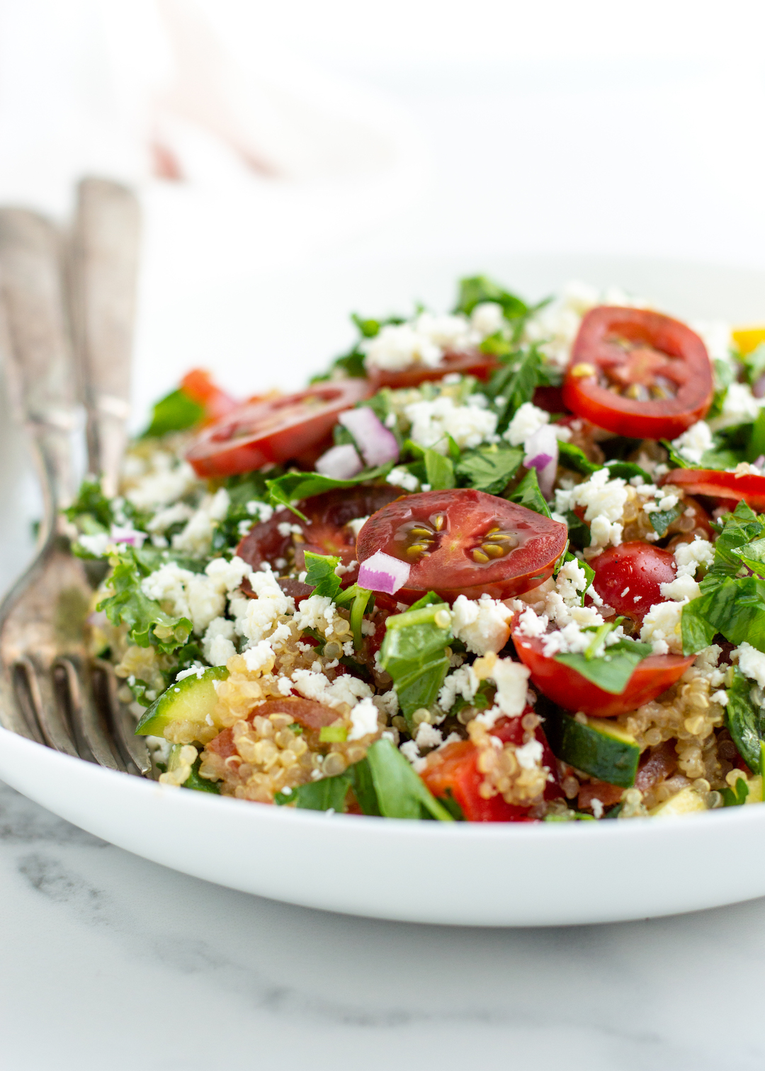 Quinoa salad doesn't get easier than this! This Easy Quinoa Salad with Garden Veggies is a simple yet protein-packed, clean eating recipe perfect for a cold lunch or healthy side for dinner. Made gluten free and vegetarian with kale, zucchini and fresh herbs and topped with a sweet citrus dressing. Best topped with lots and lots of feta cheese!
