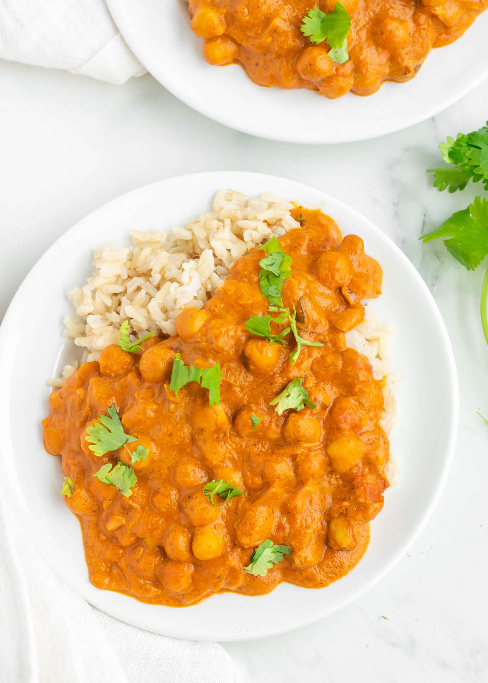 This Healthy Butter Chickpeas dish is a lightened-up, vegan and gluten free take on a classic Indian-style dish. You won't miss the chicken herre, this homemade dairy free curry is rich, creamy and satisfying made with coconut milk, tomatoes, chickpeas and a secret ingredient - almond butter! This healthy recipe is quick and easy to make for the perfect weeknight dinner any night of the week. #healthydinner #easyrecipe #glutenfree #vegan #dairyfree