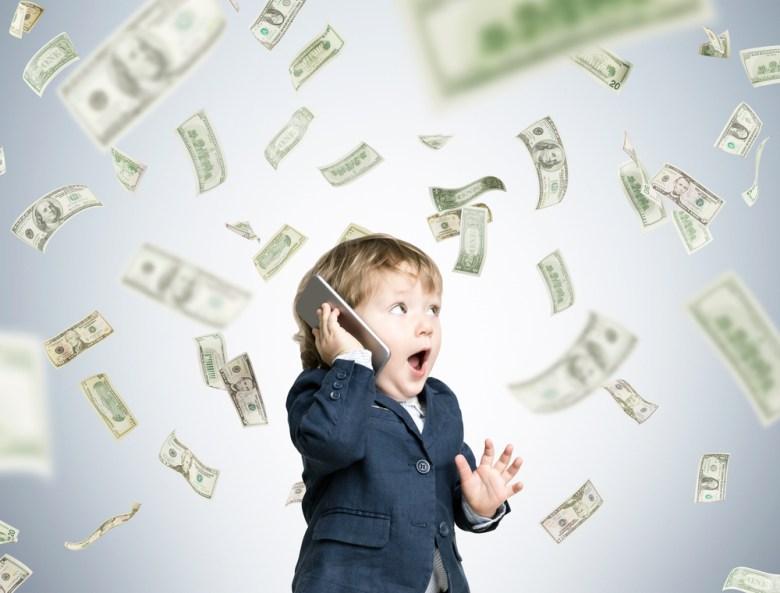 chłopiec z telefonem i pieniędzmi