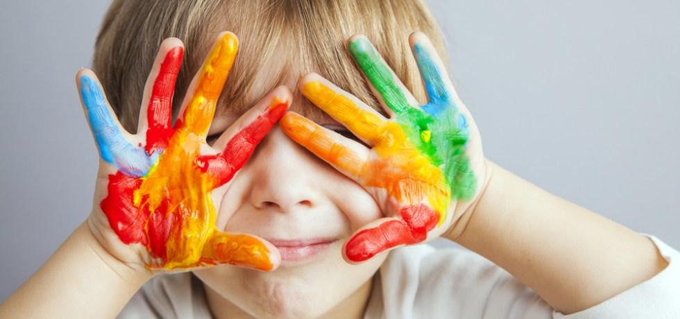 dziecko z pomalowanymi na kolorowo dłońmi