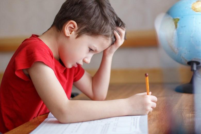 smutny chłopiec odrabiający lekcje
