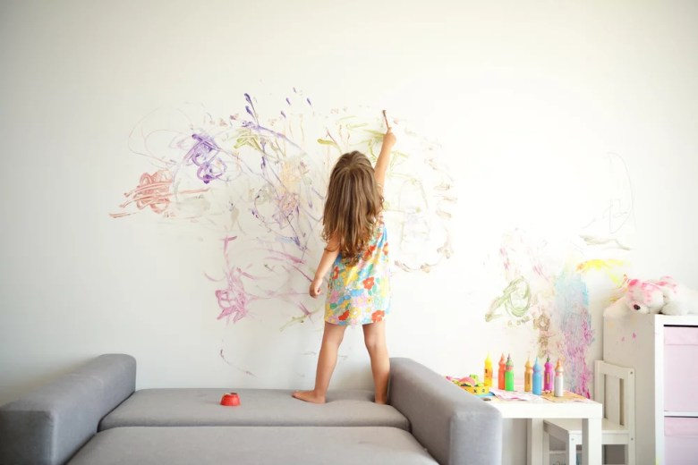 dziewczynka rysująca na ścianie w pokoju