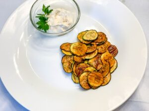 Zucchini chips on a white plate with dip
