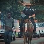 Američki policajac na konju vodi privedenog Afroamerikanca na povocu