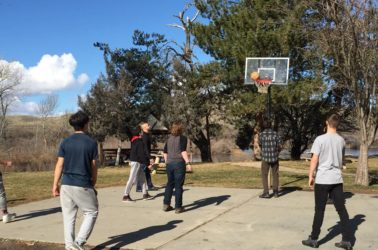 Novitas Academy students play basketball outside - one of the many activities and amenities available to students.