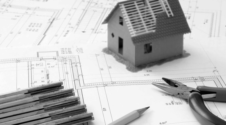 Mesa de trabajo de un Arquitecto de Experiencias con planos de arquitectura y el modelo de una casa en miniatura.