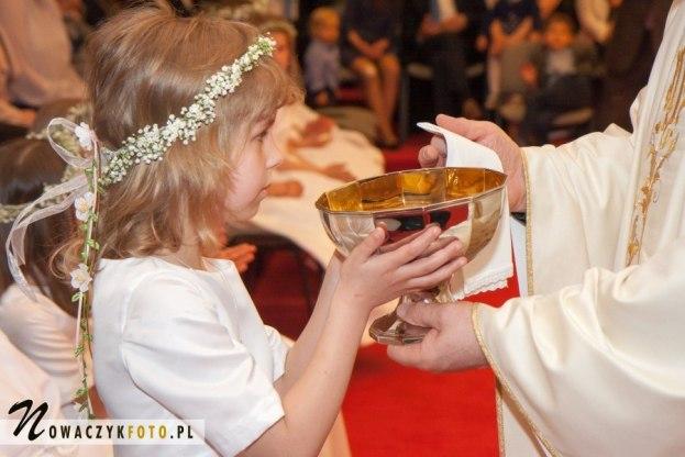 Zdjęcia komunijne dziewczynki przyjmującej krew Chrystusa