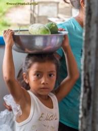 Zdjęcie dziewczynki niosącej na głowie miskę z owocami
