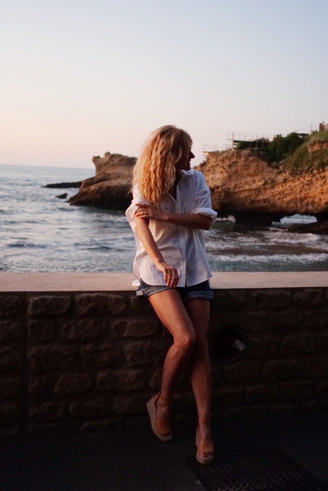 Sommerlook mit weißem Hemd von Sandro, Jeans-Shorts und Plateausandalen, Nowshine in Biarritz, Sommer 2019