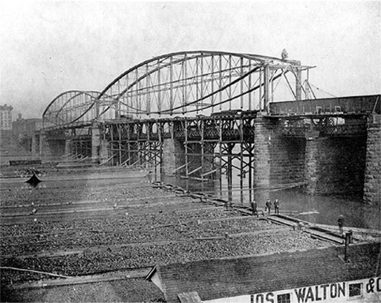 The Smithfield fish started kissing 133 years ago. Another pair joined them a few years, making the bridge wider. In this 1882 photo, the bridge it is replacing remains in operation under the fish.