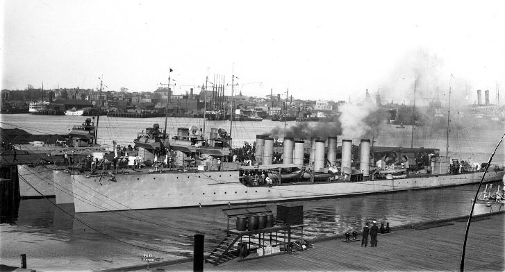 Three steel destroyers with four smokestacks are moored along a pier in the Navy Yard.