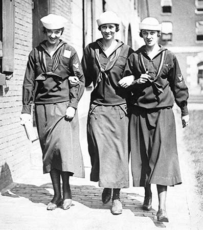 Black and white photgraph of three women walking through the navy yard in their yeoman (F) uniforms