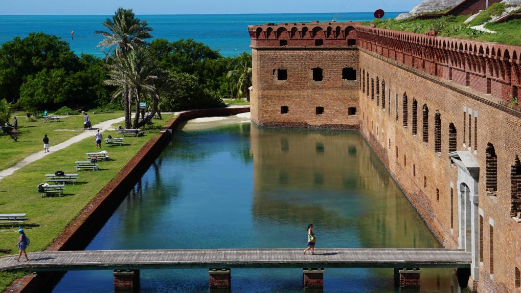 A brick structure surrounded by water, a walkway, and vegetation.