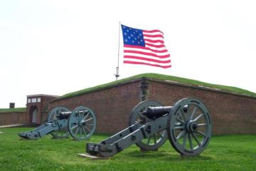 Two field pieces in front of the fort with the Garrison Flag flying.