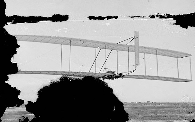 Wilbur gliding with US Lifesaving Station and Weather Station in background- Kitty Hawk, 1902