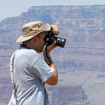 Floppy güneş şapkası giyen bir kişi, arka planda kanyon duvarları ile açık havada fotoğraf çekiyor.