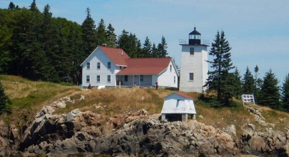 White building next to lighthouse on rocky ground with forest next to it.