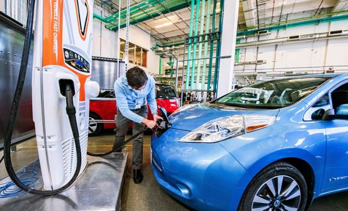 Image of an electric car inside a laboratory, charging station on the left-hand side of the photo, man is holding a charging line and placing it into a car.