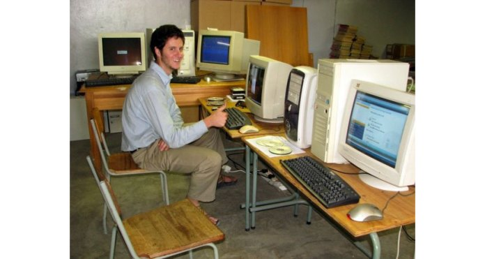 Photo of a young man sitting at a computer with a smile and giving a thumbs up. Several other computers surround him.