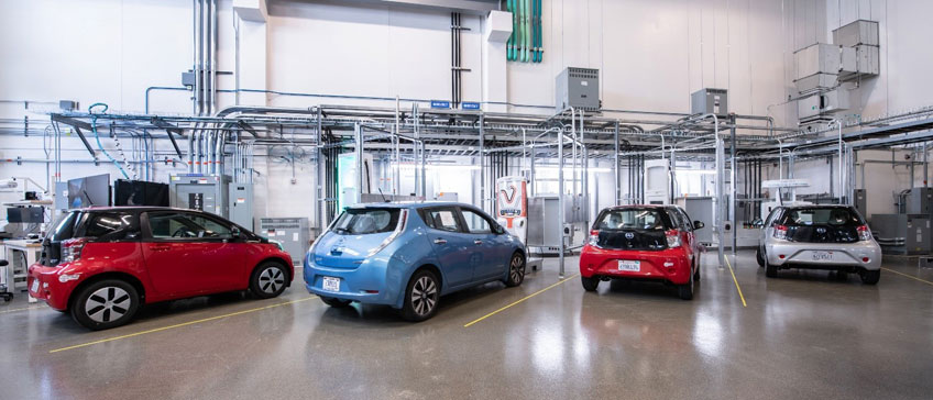 Cuatro vehículos eléctricos estacionados en una instalación interior.