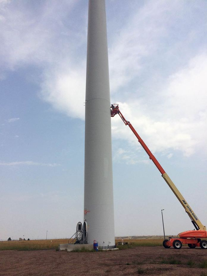 A crane with a man atop it installs UV lights on a wind turbine tower.