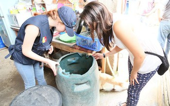 Two women looking at water accumulated in a plastic barrel in a household