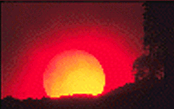 Photo of a red sun on the horizon with silouetted landscape in foreground.