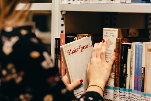 Student choosing a book in a library