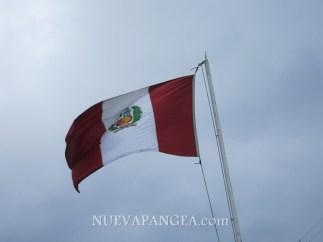 Bandera del Perú sobre el cielo nublado de Lima