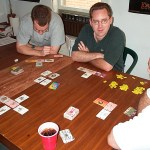 A group of male gamers plays a non-collectible card game.