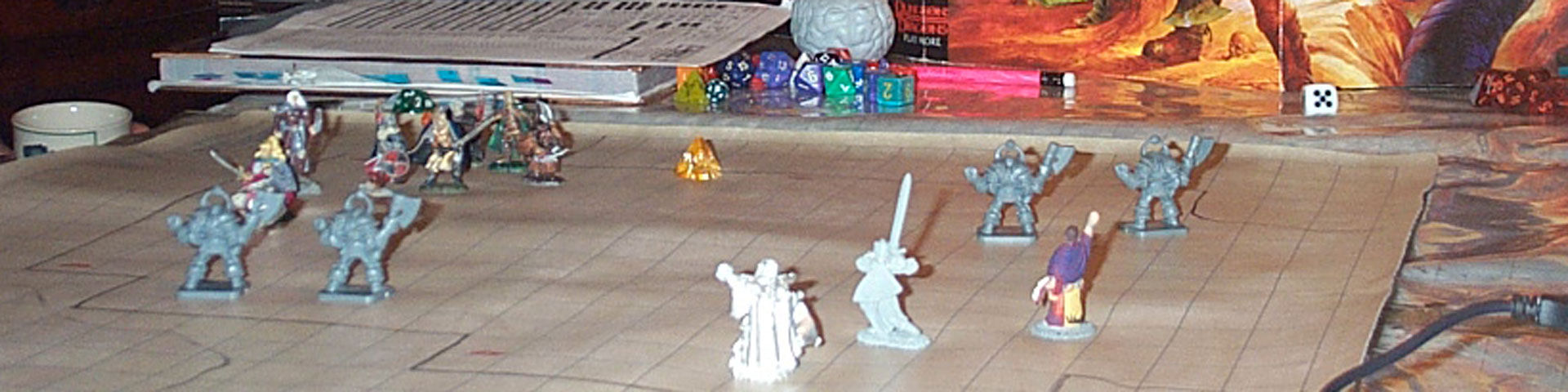 A close-up view of small fantasy figures on a gridded battle map.
