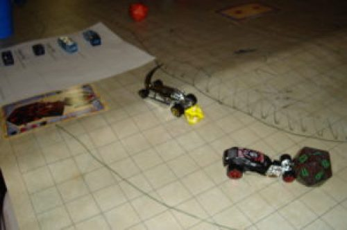 Two small Matchbox cars race across a square grid. Multisided dice indicate initiative; a character sheet can be seen to the left.