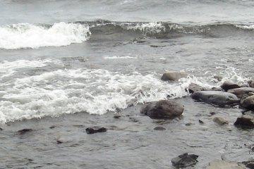 Waves rush in toward a stony shore.