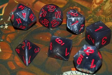 Black and grey dice with red numbers sit on top of role-playing game source books.