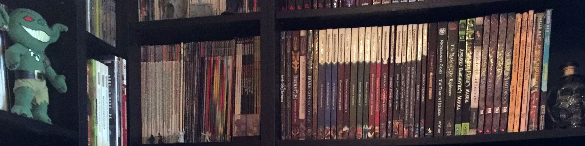 A variety of role-playing games (and one Pathfinder goblin) stand on a black bookshelf.