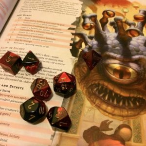 Swirling red and black dice sit on one of the Dungeon Master Guide's many random tables. A beholder stares menacingly at a terrified adventurer.