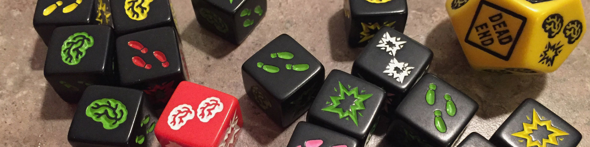 """Black and red dice feature one of three symbols: brains, footprints, or shotgun blast. A larger yellow die has """"dead end"""" printed on it."""