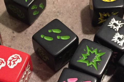 "Black and red dice feature one of three symbols: brains, footprints, or shotgun blast. A larger yellow die has ""dead end"" printed on it."
