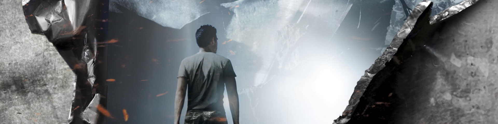 A man stands at the opening of a steel cavern. Light radiates from deeper within the cave.
