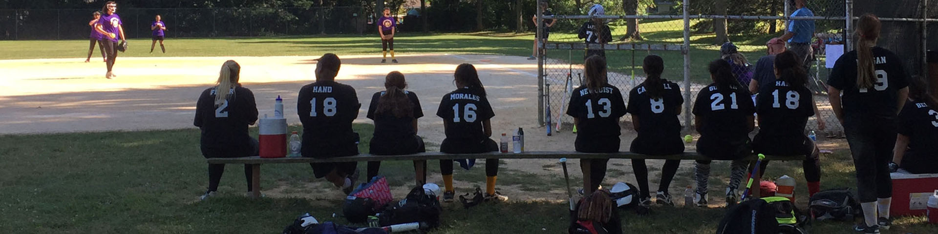 Girls in softball uniforms sitting on a bench.