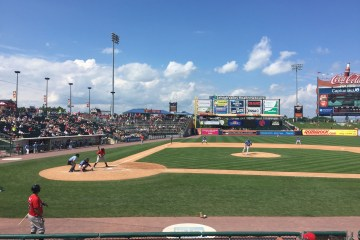 A minor league baseball team plays a game on a beautiful, mostly-sunny summer day.