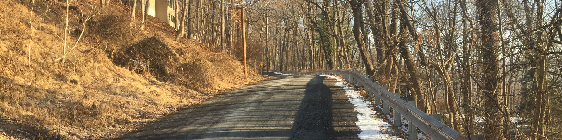 A back country road, with a thin line of snow on the right shoulder.