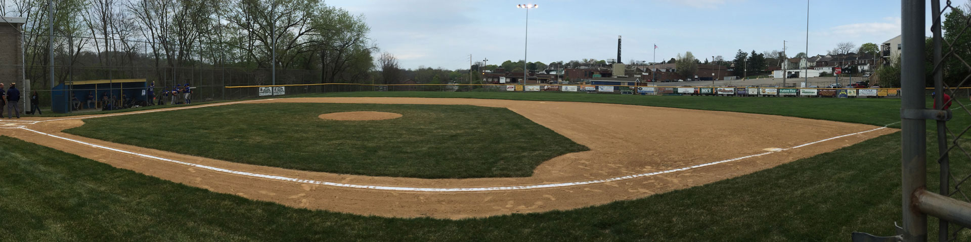 A baseball field in early spring. The field is green, but little else is.