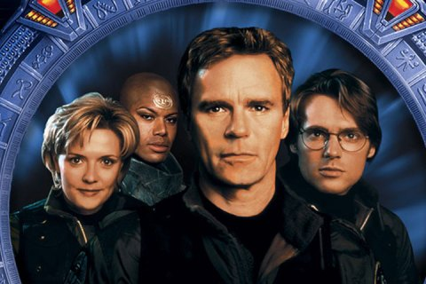 Four actors - one woman and three men - are centered on a large circular Stargate.