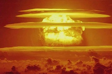 A nuclear mushroom cloud rises through the atmosphere, glowing yellow against the orange sky.