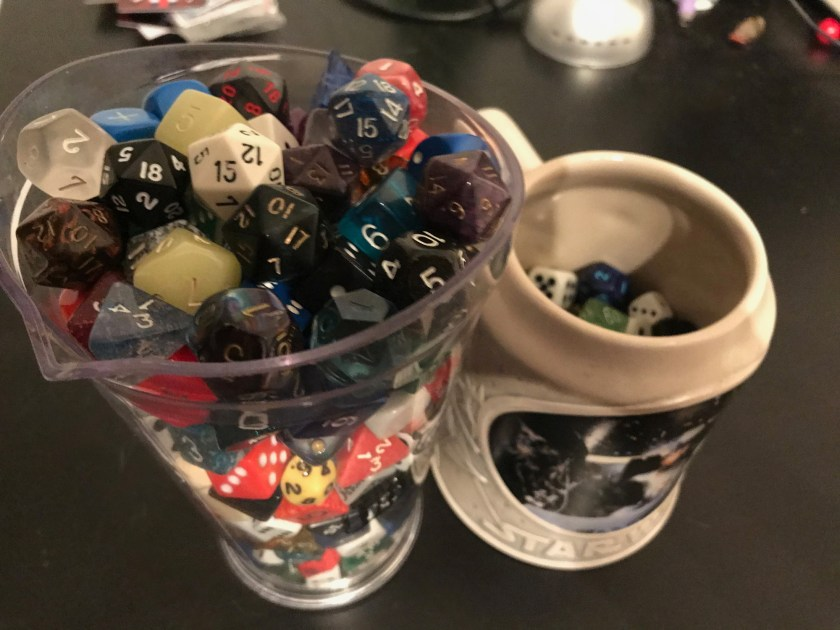 A large plastic pitcher and a ceramic mug filled with dice.
